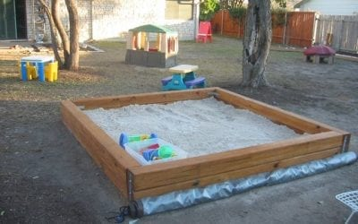 A child raking a sandbox next to his nanny
