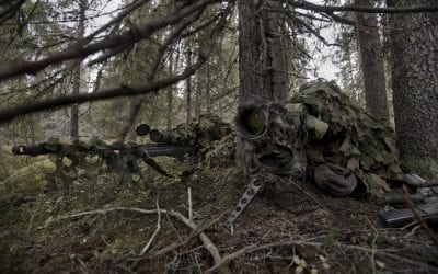 A man lying on a hill looking through a rifle scope
